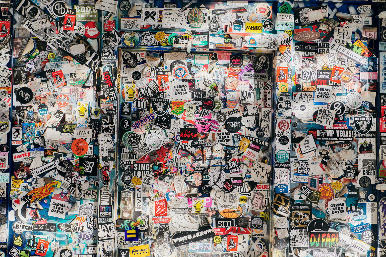 A door and wall plastered in hundreds of colorful stickers