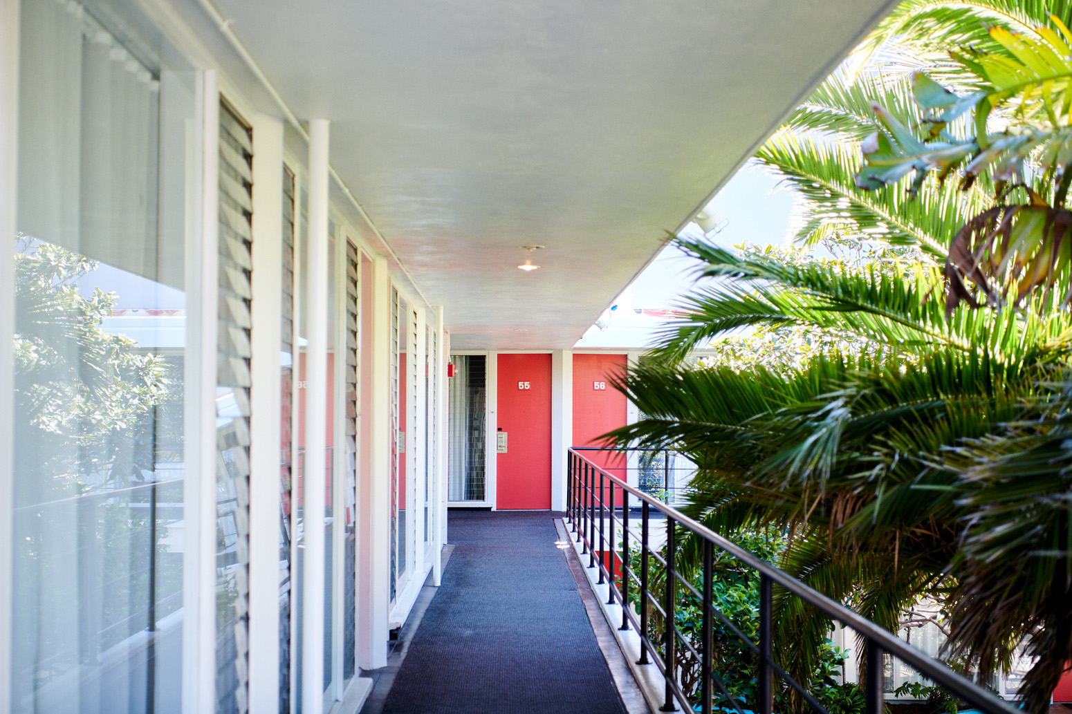 Daytime exterior view of red hotel room doors